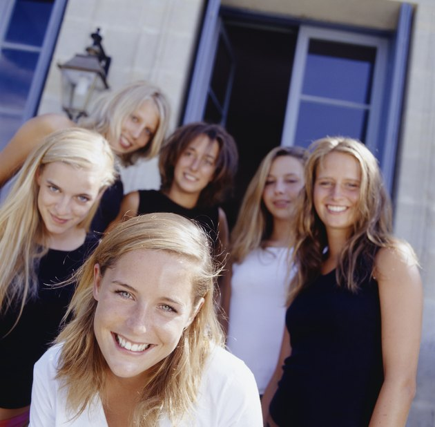 Group of young women standing in front of house, portrait