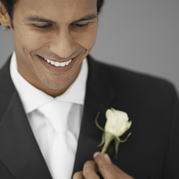 close-up of a groom holding a white rose