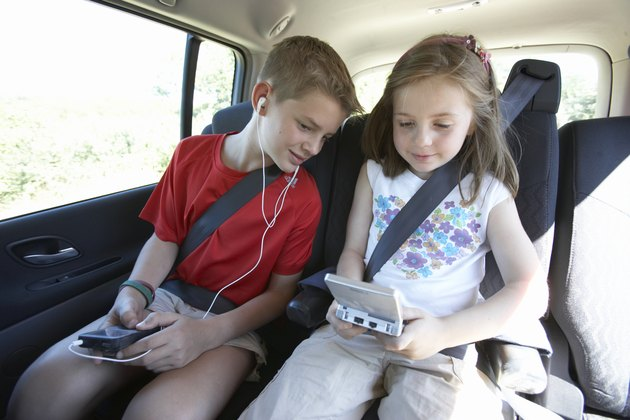 Boy (11-13) listening to mp3 player and girl (7-9) playing video game in car