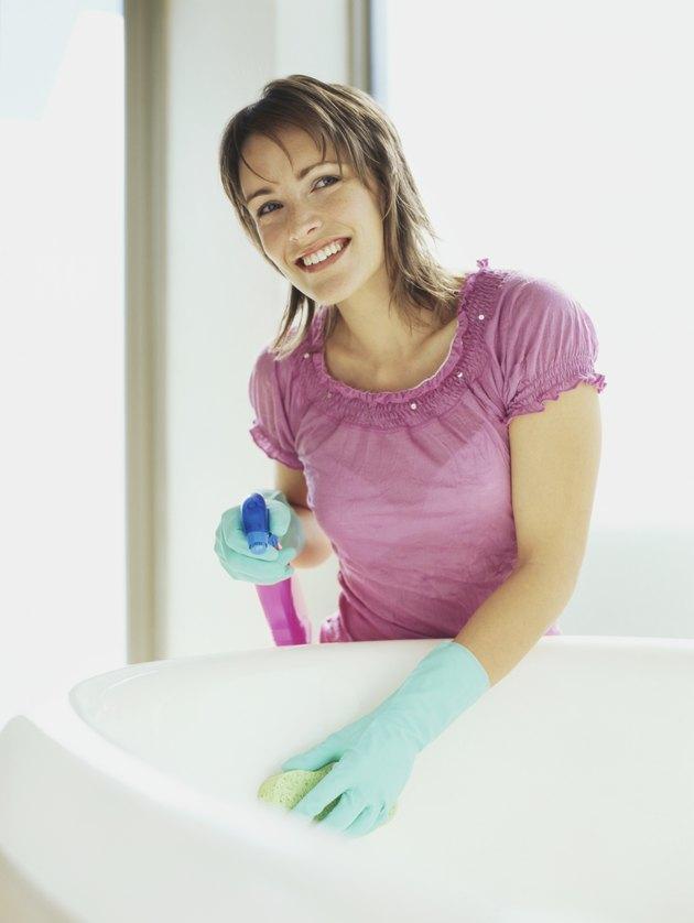 Young woman washing a bathtub