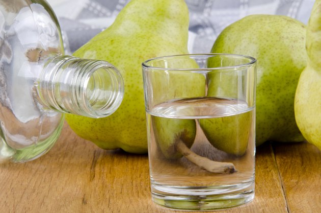 fruit brandy in a glass and fresh pears