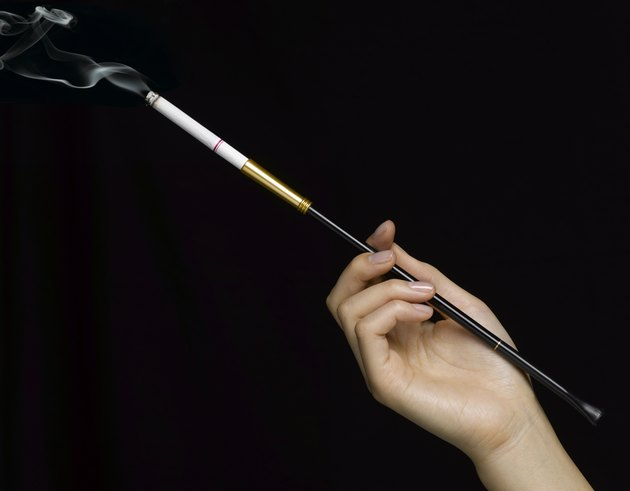 Woman holding cigarette in holder, close-up of hand