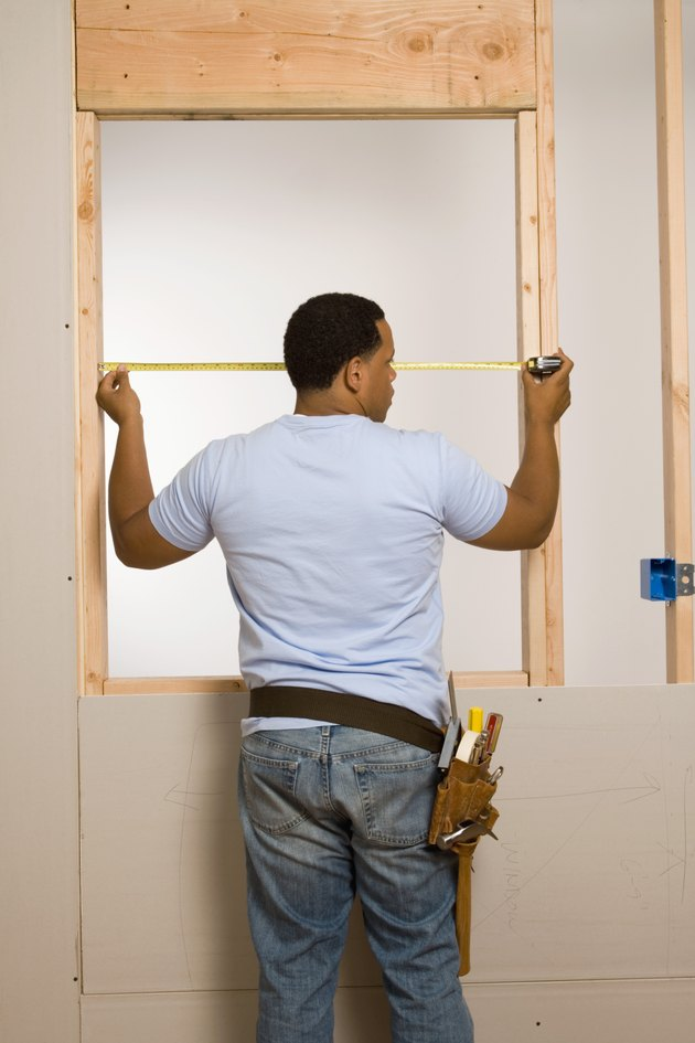 Man measuring window frame