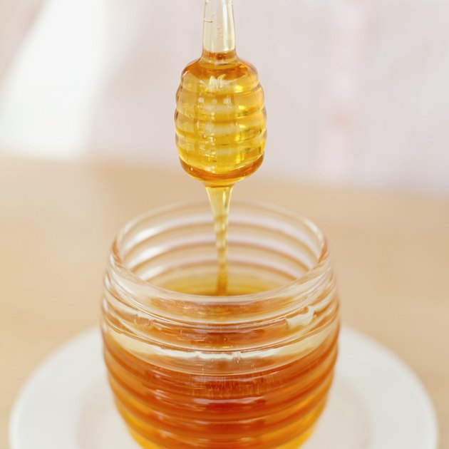 close-up of a honey dipper over a jar of honey