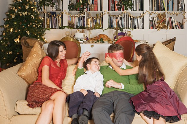 Family playing on sofa at Christmas