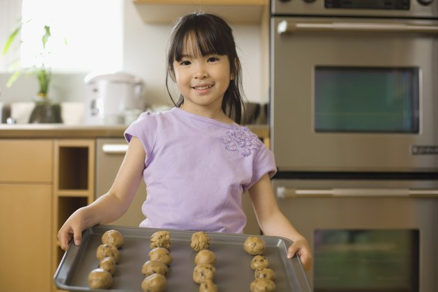 Girl holding cookie sheet