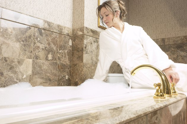 Woman sitting by bubble bath