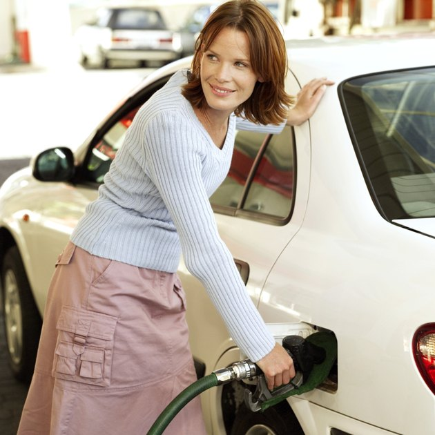 portrait of a young woman filling her car with petrol