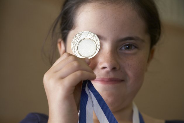 Girl (9-11) holding sports medal in front of eye
