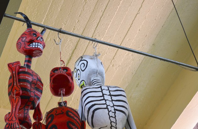 Catrina and devil hanging from ceiling at mexican market