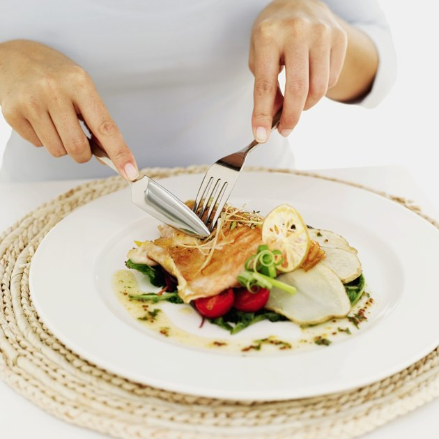 person using a fork and knife on a plate of grilled salmon