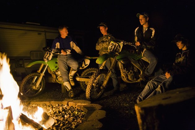 Riders on dirt bikes by campfire