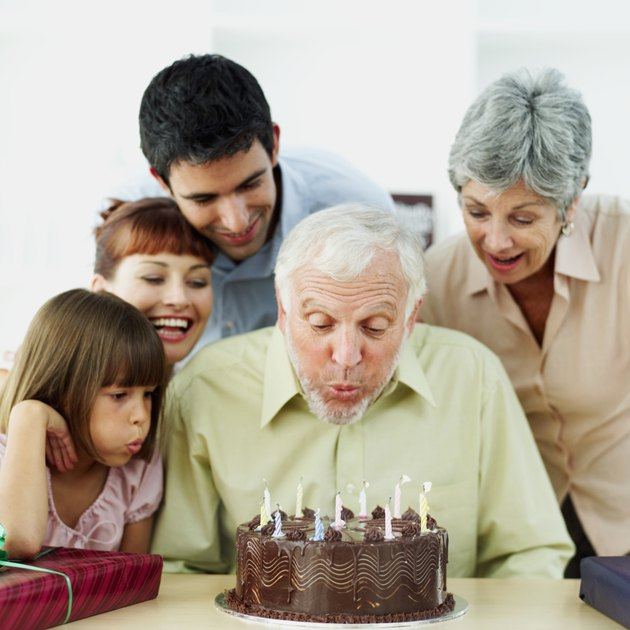 close-up of a senior man blowing candles on a birthday cake with his family standing behind him