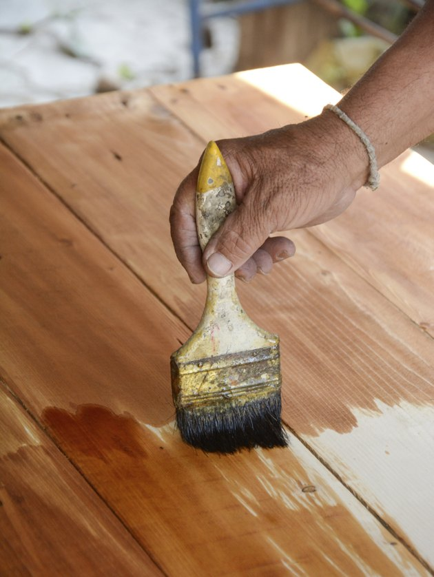 carpenter s hands paintbrush varnish to wood table