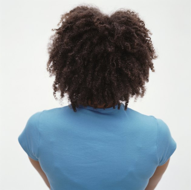 Young woman with frizzy hair, posing in studio, rear view, portrait