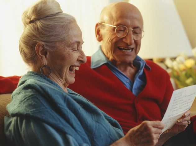 Senior couple reading letter in living room