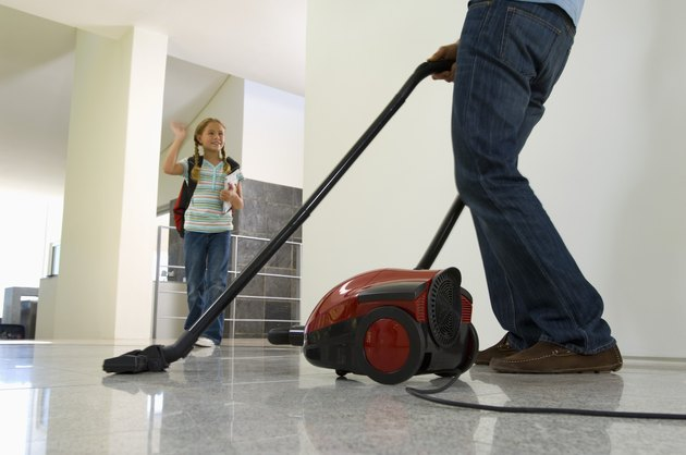 Girl waving at father vacuuming