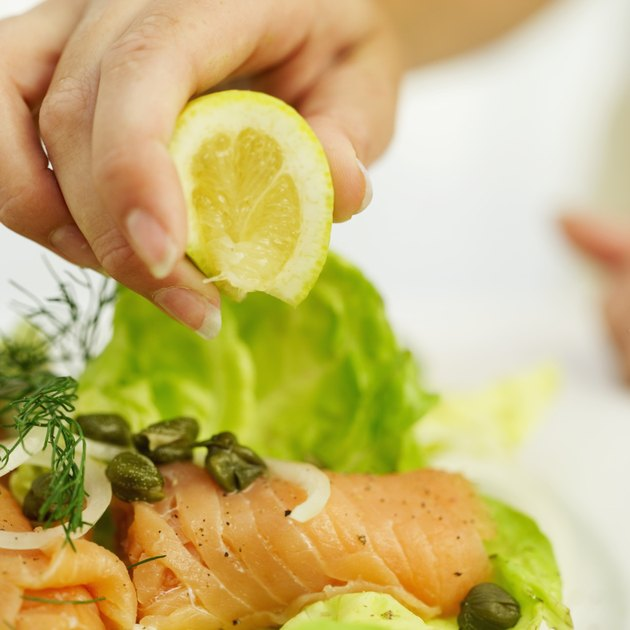 close-up of a person's hand squeezing lemon on a sushi salad