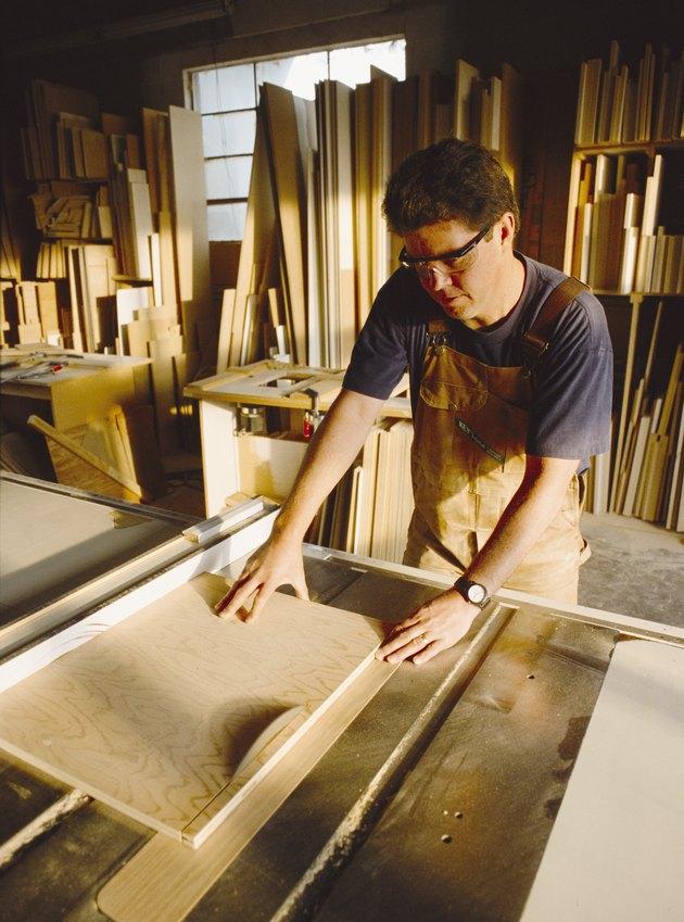 a carpenter cuts a board with a saw