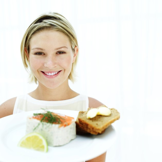 Portrait of a woman holding a plate of pate and sliced bread