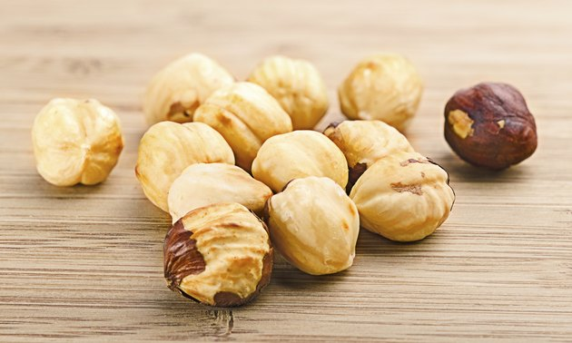 pile of shell-less hazelnuts, isolated on textural wood backgr