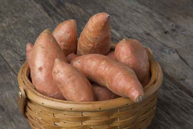 Sweet Potatoes in Basket on Wood Table