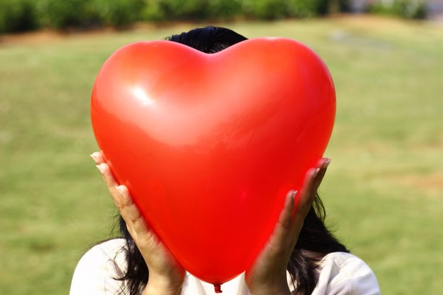 Close-up of a woman holding a heart shaped balloon covering her face