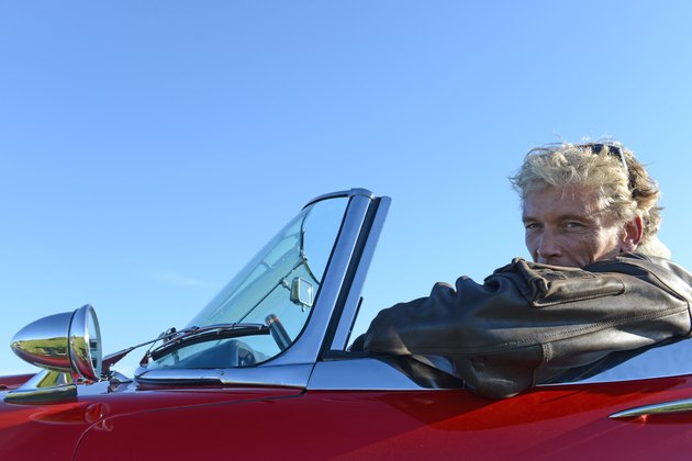 Portrait of mature man in red sports car