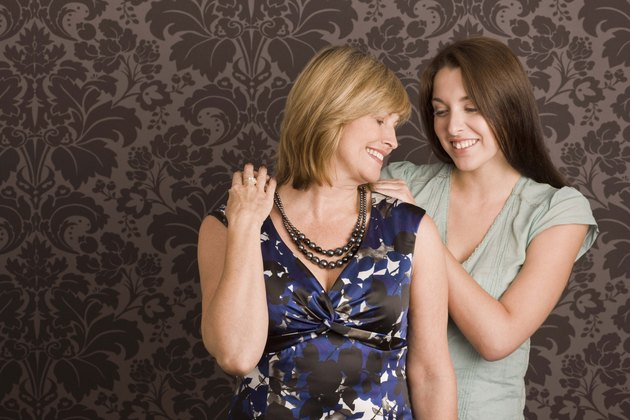 Daughter helping mother get dressed