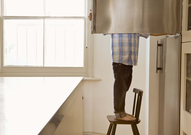 Child standing on chair opening freezer