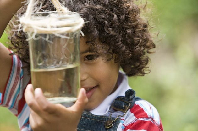 Curious boy outdoors with jar of water