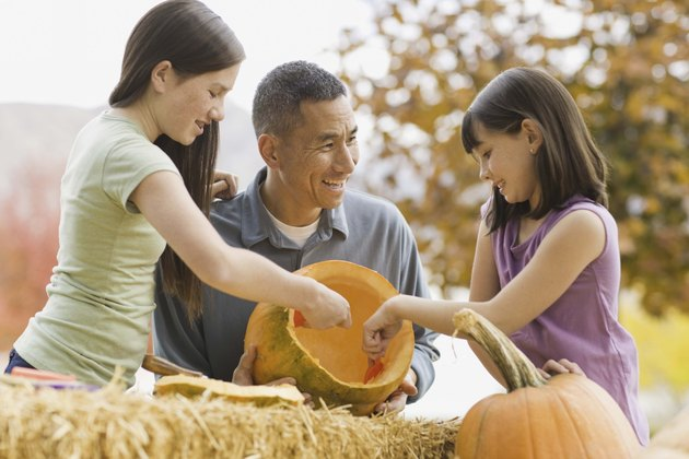 Girls and father carving pumpkins