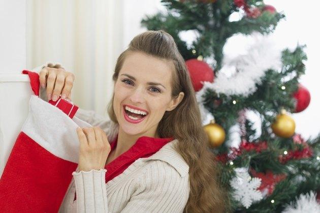 Smiling young woman checking Christmas socks