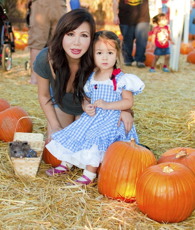 Asian mother and daughter visit a pumpkin patch, with the little one dressed up as Dorothy (from The Wizard Of Oz) for Halloween. And lets not forget her faithful little puppy in the basket.