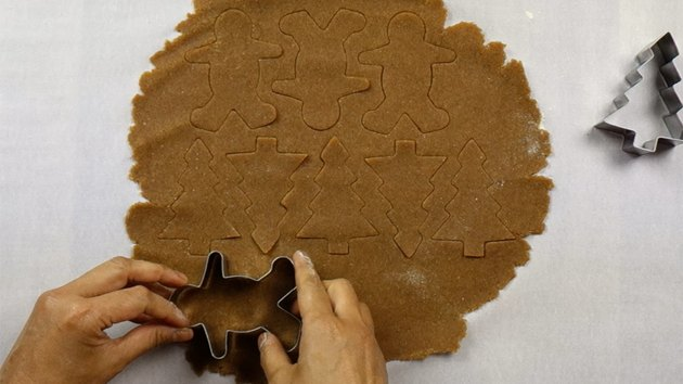 Cutting out gingerbread men and christmas tree shapes from gluten-free, low-carb gingerbread cookie dough.