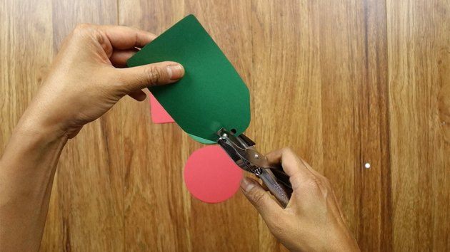Using hole puncher to make holes in DIY Christmas tags