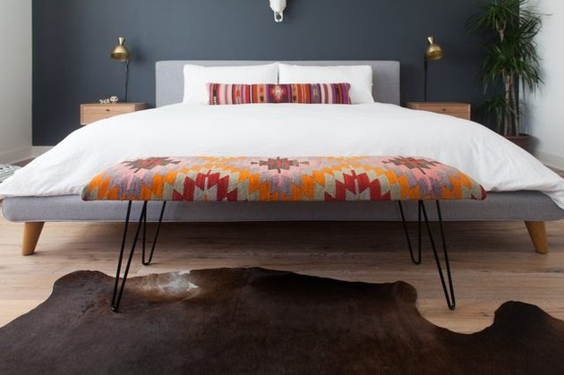 Kilim patterned rug bench at the end of a large bed