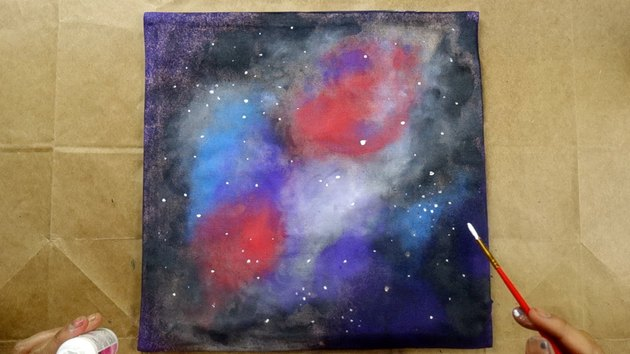 Using paintbrush to dot stars on galaxy-themed cushion cover.
