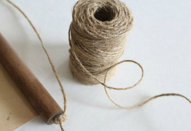 Thread twine or rope through eye hooks and tie to make a loop.