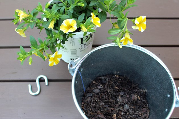add soil, flowers to galvanized paint bucket