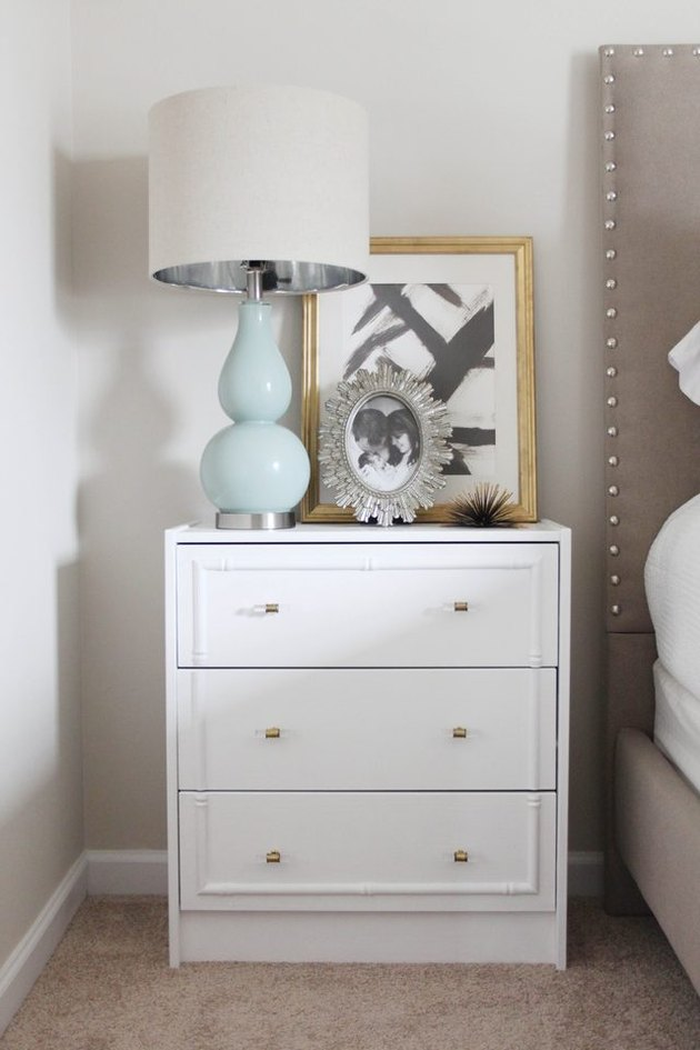 White nightstand with a blue lamp, picture, and photo frame