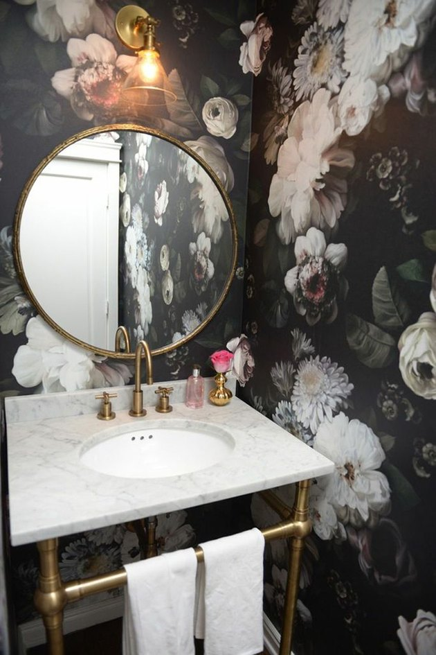 Powder room with bold floral wallpaper and scone lighting