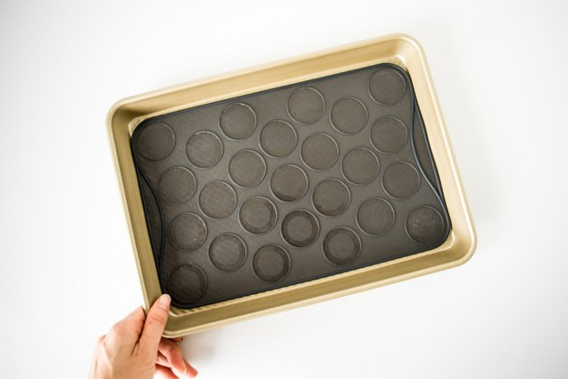 Baking tray lined with silicone macaron slip-mat.