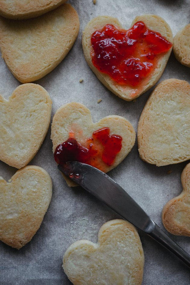 Use a knife to spread the jam over the cookie bases.