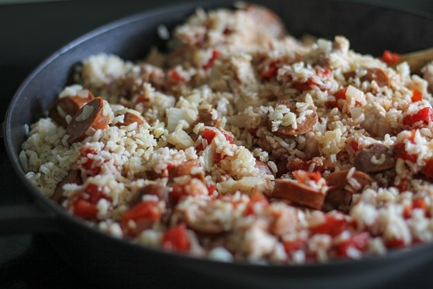 chicken, onion, rice, chorizo, and tomatoes in a paella pan