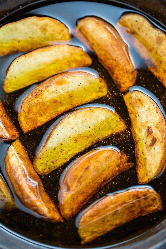 Pan frying the potato wedges in oil