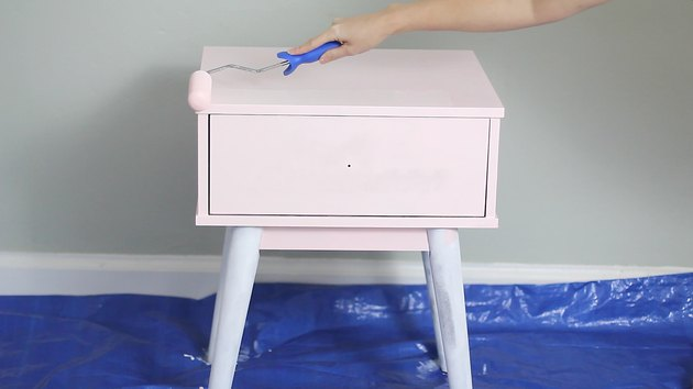 Rolling pink paint onto the nightstand