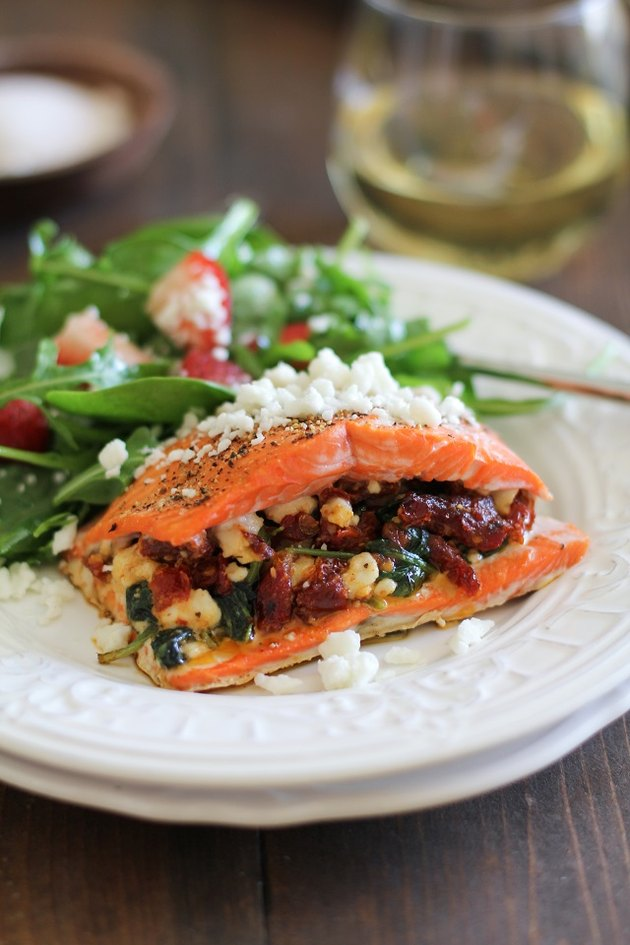 Plated stuffed salmon with spinach salad.