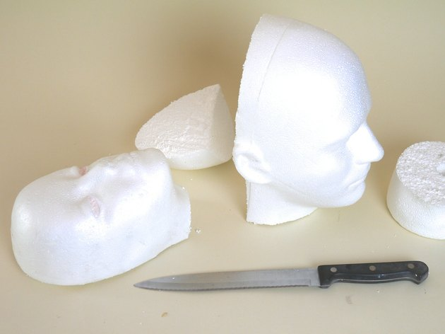 Two foam heads with their backs removed by a serrated kitchen knife.