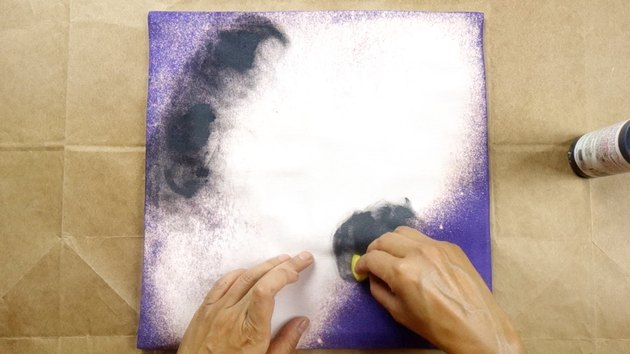 Sponging fabric paint onto cushion cover in circular motion.